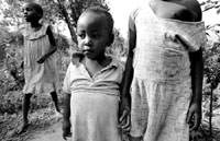 A 5 year old aunt holds the hand of  her niece, the result of the rape of the CHH
